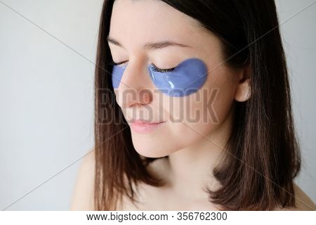 Young Woman With Under Eye Patches In Her Face. Collagen Eye Mask For Puffiness, Close-up View. Faci