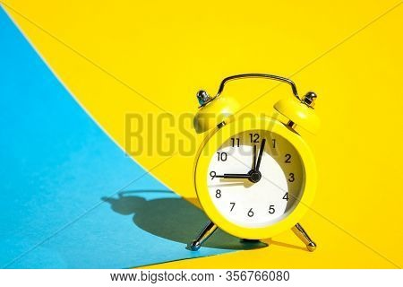 Yellow Vintage Alarm Clock On A Blue And Yellow Background With Selective Focus, Copy Space For Text