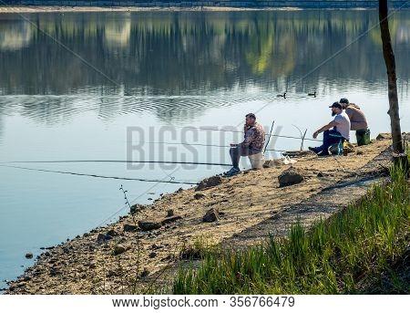 Bucharest/romania - 03.19.2020: Fisherman On The Edge Of Herestrau Lake. Man Fishing On A Sunny Day