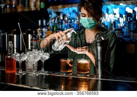 Woman In Medical Mask Treats Her Hands With Disinfector Behind Bar Counter.