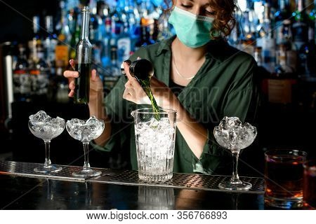 Girl Bartender In Medical Mask Pours Liquid Into Glass With Ice