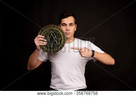 A Young Guy Holds A Symbol Of The Eos Coin, A Modern Currency For Exchange And Purchases. Photo On A