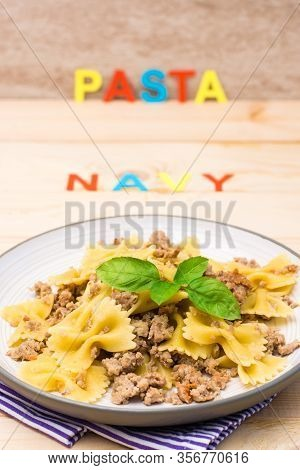 Ready-to-eat Pasta Navy With Minced Meat And Basil Leaves On A Plate And The Word