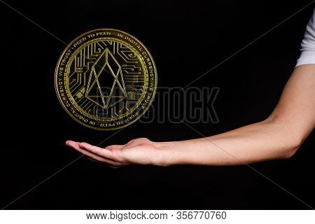 The Symbol Of The New Popular Cryptocurrency Eosio With The Image Of Hands On Dark Background