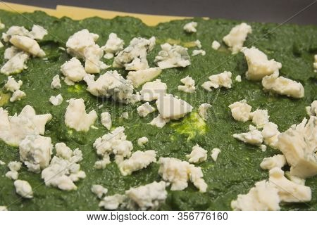Spinach And Moldy Cheese On Raw Lasagne Pasta In Baking Sheet