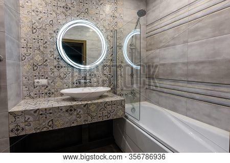 Washbasin, Mirror And Bathtub In The Interior Of A Modern Bathroom