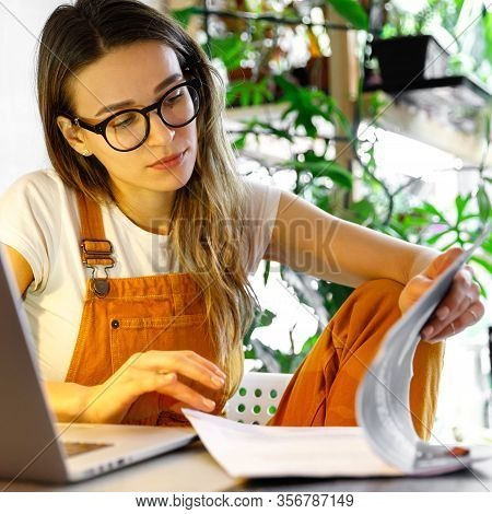 Young Female Gardener In Glasses Using Laptop, Makes A Report On Office Documents, Works From Home D