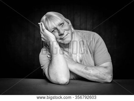 Black And White Seated Portrait Of A Blonde Trans Woman Resting Head On Her Hand