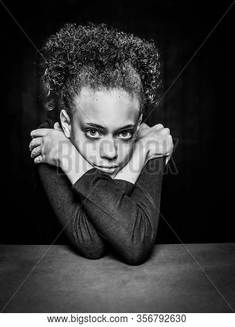 Black And White Vertical Shot Of Pretty Young Girl Resting Her Head On Crossed Arms