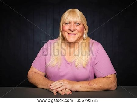 Seated Portrait Of A Smiling Blonde Trans Woman