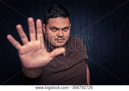 Latino Man Using An Open Hand To Make A Stop Gesture