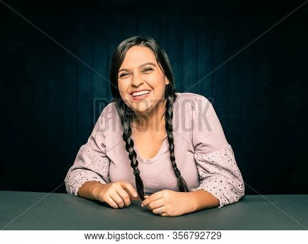Portrait Of Happy Laughing  Young Woman Leaning On Table With Hair In Braids