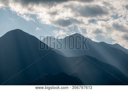 A Sunray Shining Through The Clouds On A Hill