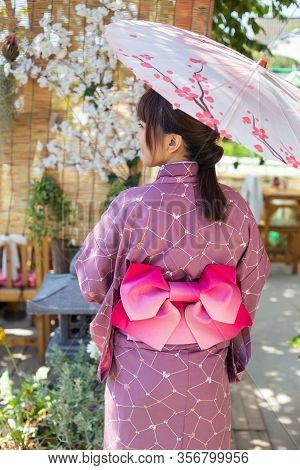 The Girl Is Wearing A Pink Traditional Yukata, Which Is The National Dress Of Japan And Hold An Umbr