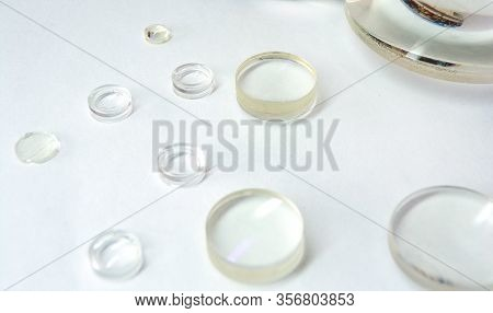 Lenses. Glass Lenses Are Isolated On A White Background. Small Optical Magnifying Lenses Close-up. S