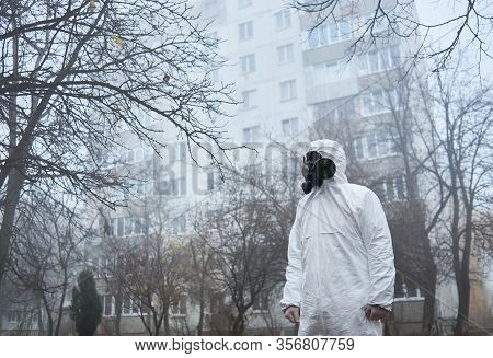 Side View Of Ecologist In Protective Uniform Standing On Foggy Street And Looking Aside. Male Enviro