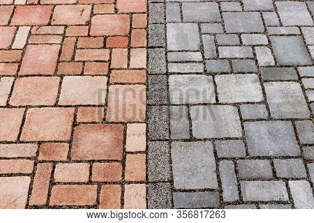 Red And Gray Brick Paving Stones On A Sidewalk. Separation Of Bike And Footpath