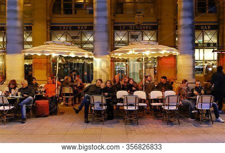 Paris, France - March 12, 2020 : Parisians And Tourists Sit On The Terrace Of Le Nemours Cafe. This