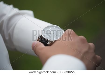 Close Up Of Businessman Looking At Watch On His Hand Outdoors, Free Space. Man In White Shirt Checki