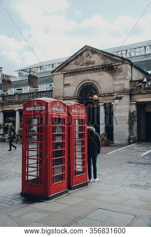 London, Uk - March 06, 2020: Red Phone Box Covent Garden, Market On The Background. Red Phone Boxes