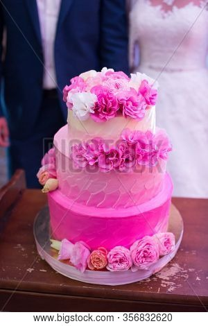 Pink Three- Tiered Wedding Cake With Fresh Flowers.