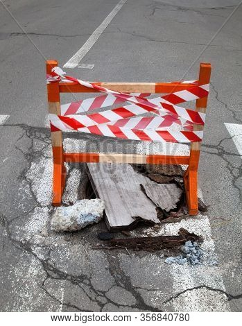 Pothole On The Pedestrian Crossing On The Road. Wooden Safety Barrier With Safety Strip Above The Po