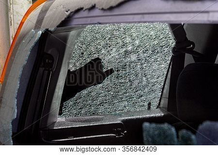 Broken Car Glass In An Accident. Damaged Automotive Glass Background Pattern. Broken Car As A Result