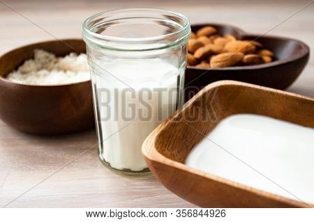 Almond Milk In A Glass, Almonds, Milk And Squeezed Nut In Bamboo Bowl On Wooden Background Close Up