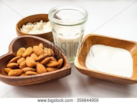 Almond Milk In A Glass, Almonds, Milk And Squeezed Nut In Wooden Bowl On White Color Background Clos