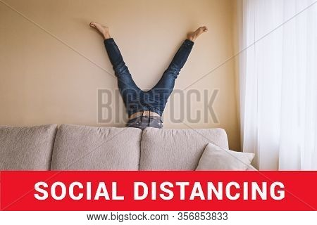 Man Handstanding Behind Couch. People Goes Crazy In Quarantine. Mens Depression Concept Social-isola