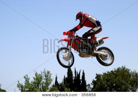 Motor Cross Bike Leaping Through The Air On A Hot Sunn