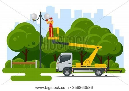 Yellow Engine Powered Scissor Lift. Worker With The Help Of An Automobile Tower Change Repairing A S