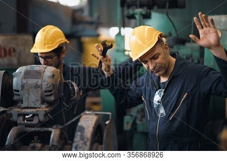 Shot Of Two Industrial Workers Feeling Bad With Old System In The Factory, The Worker Feels Upset An