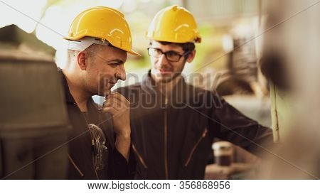Scene Shot Of 2 Industrial Workers Discussing About Planning, The Procedure Of Work In The Factory W