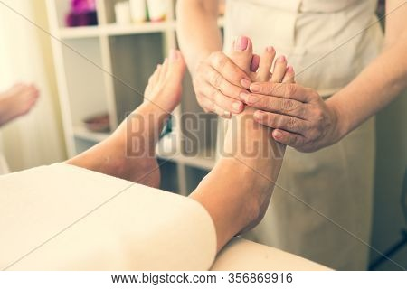Close Up Of Masseuse Giving A Foot Reflexology Treatment In A Natural Light Tone In A Spa Salon, Con