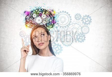 Young Woman With Long Fair Hair Pointing Upwards Standing Near Concrete Wall With Colorful Brain Ske