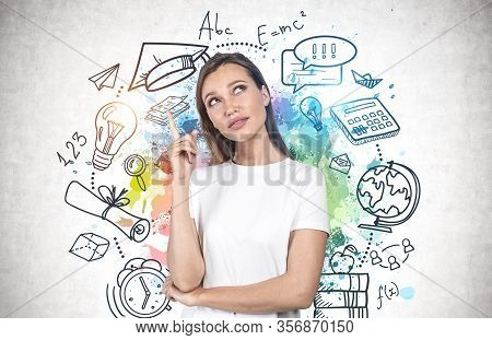 Thoughtful Young Woman With Long Fair Hair And Bright Idea Pointing Upwards Standing Near Concrete W