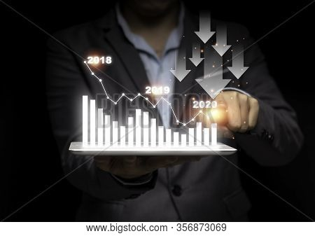 Businessman Hand Point Drawing Decrease Trend Arrow For Economic Crisis In 2020 On Black Background.
