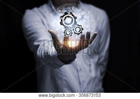Businessman Hand Holding Cog Gear Wheel Infographic With Sunlight. Engineering Creative And Business