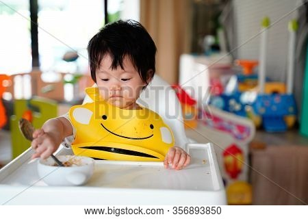 Toddler Eats Herself In Highchair And Wearing Apron. Baby Try To Use Spoon Putting Into  Bowl,her Fa