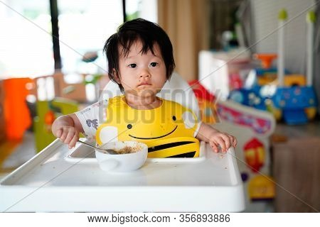 Toddler Eats Herself In Highchair And Wearing Apron.baby Look Up And Try To Use Spoon Putting Into