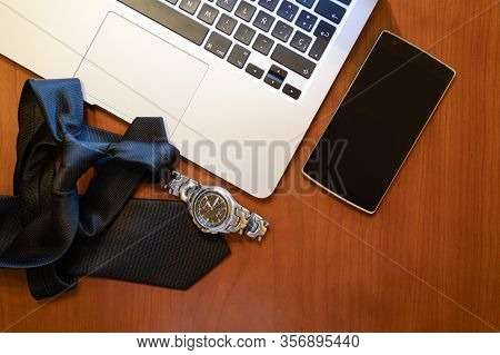 Smart Phone, Wristwatch And Laptop On Elegant Wooden Table,