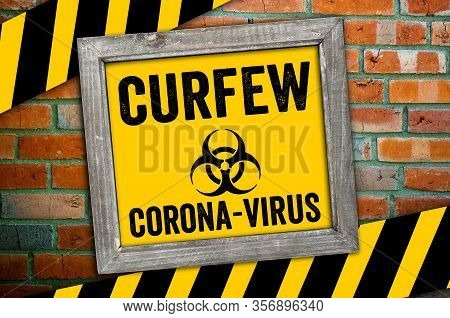 Sign In Front Of A Clinker Wall With Curfew And Corona Virus Biohazard
