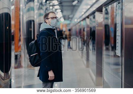 Horizontal Shot Of Man Traveler Poses On Metro Station, Wears Medical Mask During Coronavirus Time,