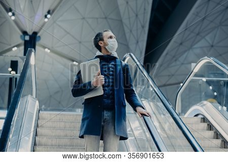 Shot Of Man Tourist Poses On Escalator In Airport, Arrives Home From Abroad During Virus Outbreak, W