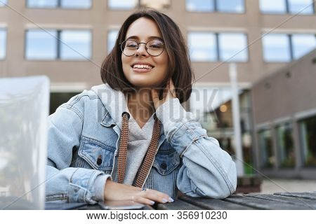 Close-up Portrait Of Young Attractive Queer Girl In Denim Jacket, Student Sitting Outside With Lapto