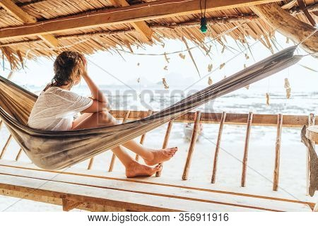 Young Female Sitting In Hammock On Straw Hut Terrace And Enjoying A Seaside Beach Landscape On Tonsa
