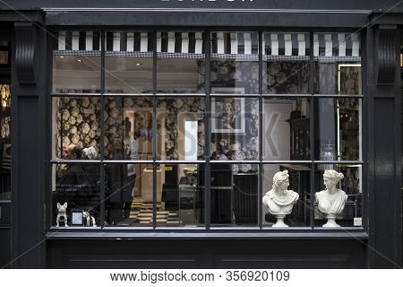 London, Uk - March 20, 2020: Facade Of A Barber Shop With Traditional Black Windows And Two Plaster