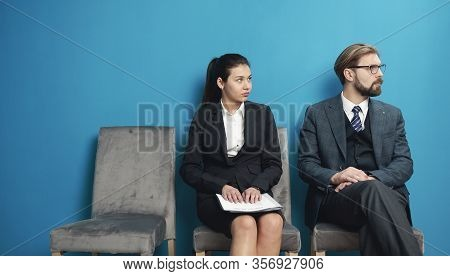 Man And Woman Job-seekers Waiting For Intake Meeting Sitting In Row And Both Looking Aside