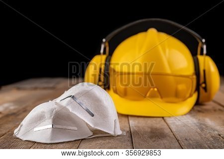 Workwear And Protective Mask On A Wooden Table. Protective Accessories For The Production Worker.